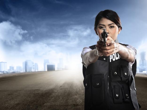 Красивая полицейская женщина держит пистолет