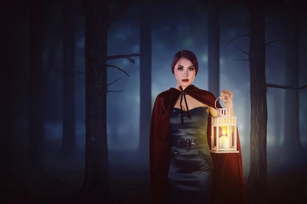 Молодая азиатская женщина ведьмы с красным плащом гуляя в пущу с фонариком