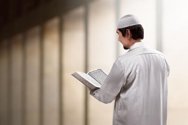 アジアのイスラム教徒の若者がコーランを読む