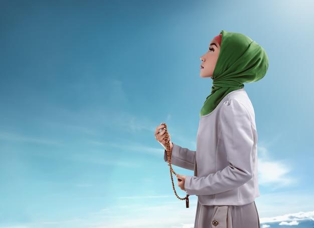祈りビーズを保持している若いイスラム教徒の女性