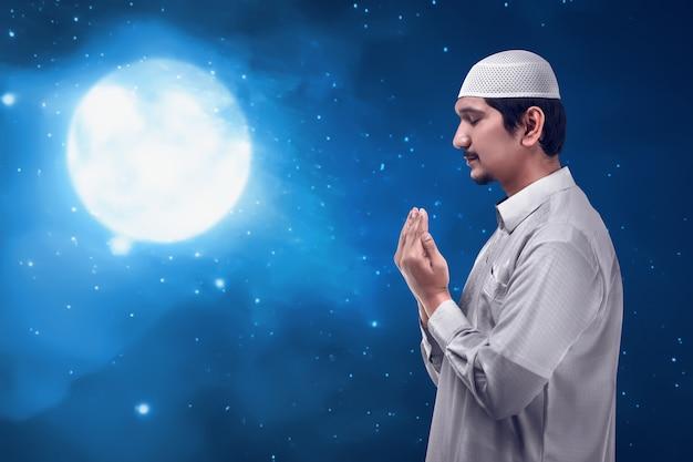 若い男がアジアのイスラム教徒の祈り