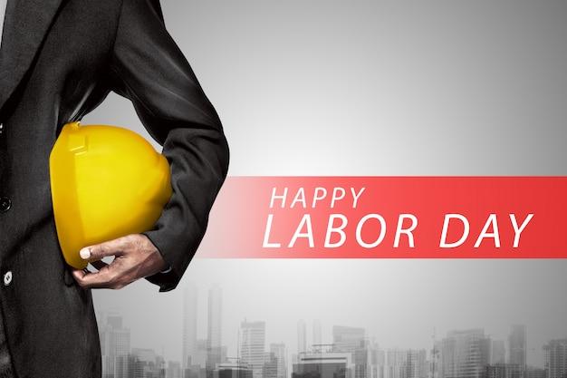 エンジニアの手や腕は労働者のための黄色のプラスチック製のヘルメットを握る