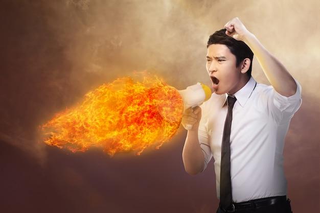ビジネスの男性が火でメガホンを押しながら叫んで