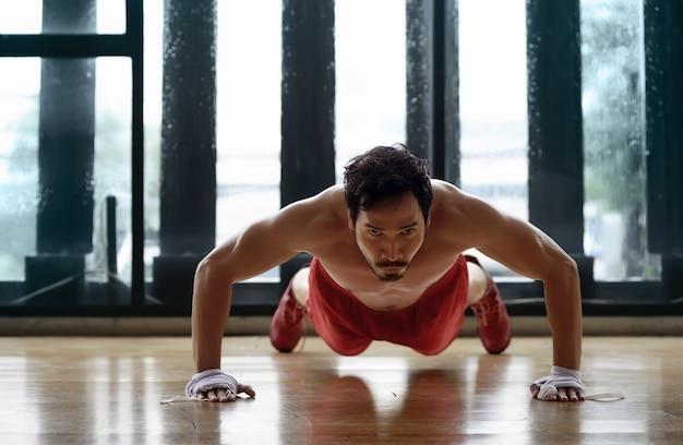 筋肉のアジア人男性が腕立て伏せ
