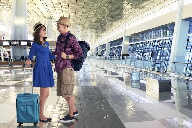 Счастливая азиатская пара собирается отпуск с чемоданами и сумкой
