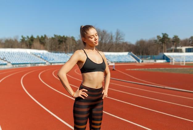 若いフィットネス女性ランナートラック上を実行する前にウォームアップ