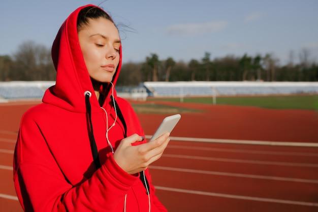 赤いパーカーを着ている若いスポーツ女性の側面図です。