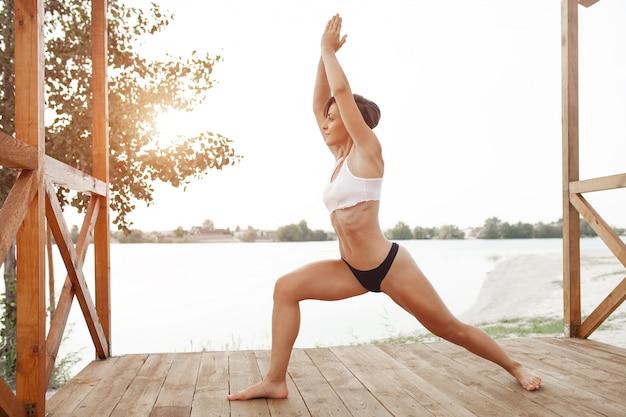 短い髪の美しい運動少女は湖でスポーツをします。ハタヨガで戦士のポーズ