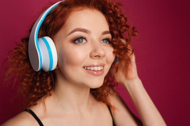 ヘッドフォンで美しい巻き毛の赤い髪の少女。クローズアップの肖像画