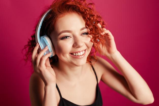 大きなヘッドフォンでかわいい若い赤毛の女の子をクローズアップの肖像画
