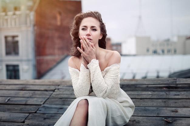 美しい少女は屋根の上に座って悲しい。