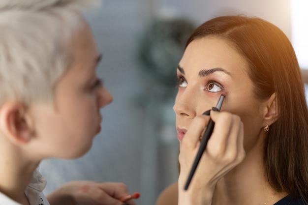 Визажист наносит яркие тени базового цвета на глаза модели