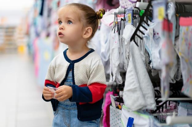 小さな白人の女の子が大きな店で服や下着の店の窓の近くに立っています。