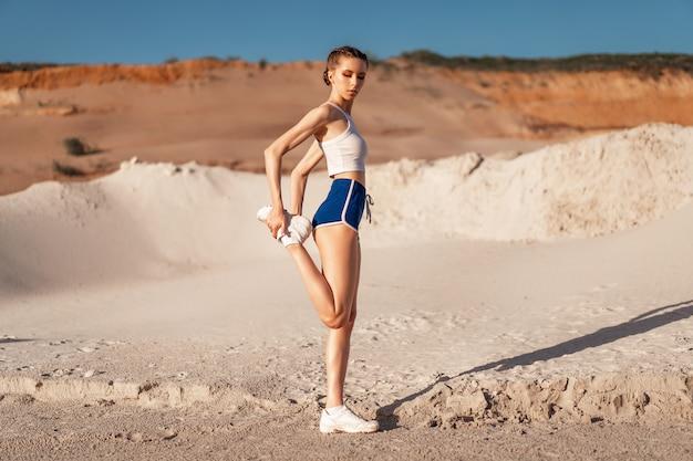 若い女性の足を伸ばし、自然でウォーミングアップ。フィットネスの前に広がる魅力的な女の子。屋外フィットネスを行うスポーティな美少女。セクシーなカジュアルなスポーツウェアに身を包んだ。