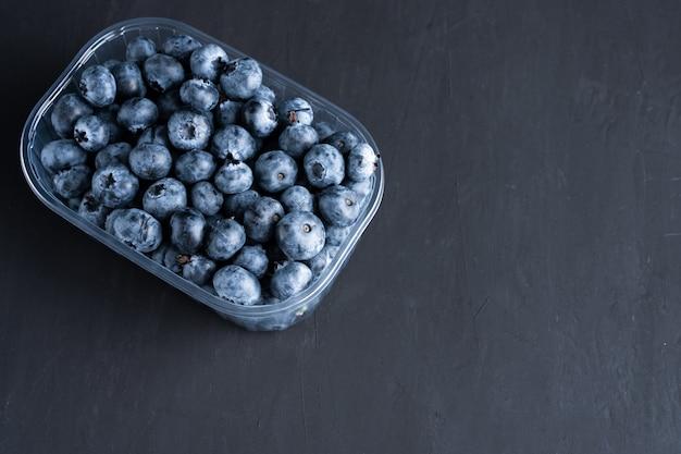 Вкусные сочные сырые ягоды черники в пластиковом контейнере. упаковка для ягод в супермаркете на полках магазинов.