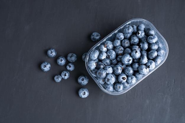 Вкусные сочные сырые ягоды черники в пластиковом контейнере