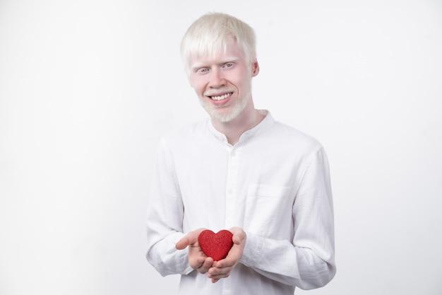 Портрет человека альбиноса в студии одел футболку изолированную на белой предпосылке. ненормальные отклонения. необычная внешность. аномалия кожи
