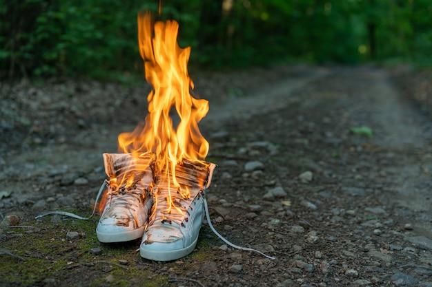 使用済みの白いハイスニーカーは田舎道と火の上に立つ