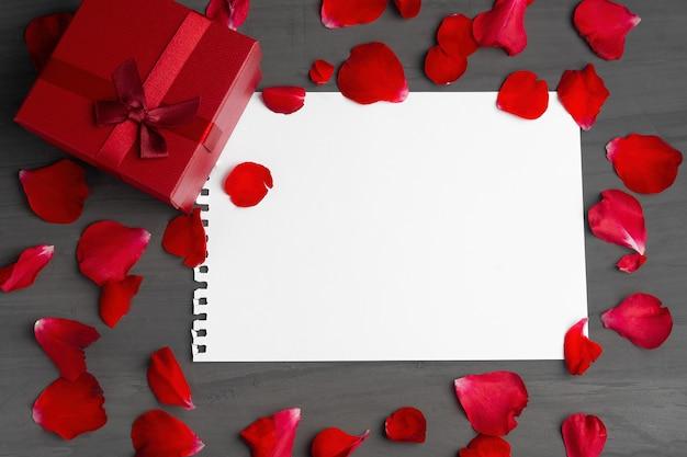 Пустой лист бумаги для текста и красной подарочной коробке