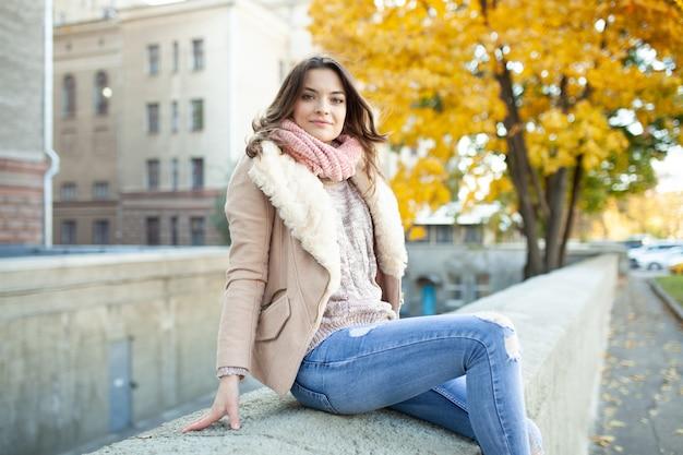 黄色の葉と都市の木の背景と暖かい秋の日に座っている美しい白人ブルネットの少女