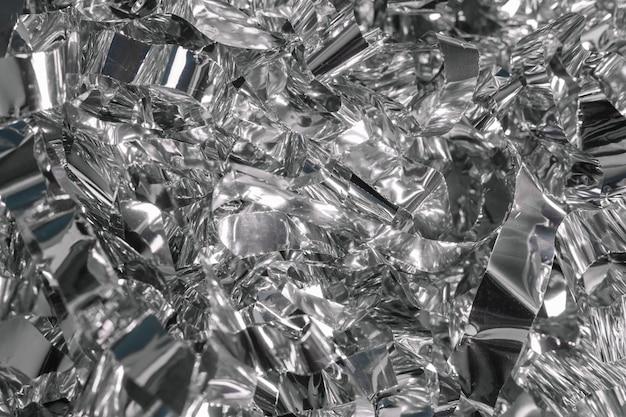 休日の包装のための銀の光沢のある金属箔の背景