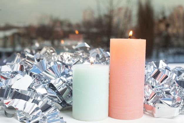 Зимний декор на подоконнике с двумя свечами и серебряной фольгой