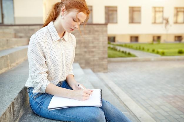 若い美しい学生は屋外階段の上に座って彼女のノートにエッセイを書く