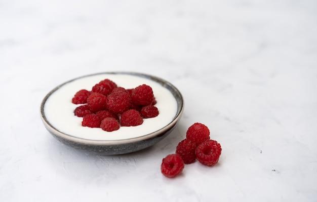 白いテーブルの上に立ってセラミックボウルでおいしい新鮮なラズベリーヨーグルトシェイクデザート。自家製ベリーのスムージー。健康的な食事。ダイエット食品。
