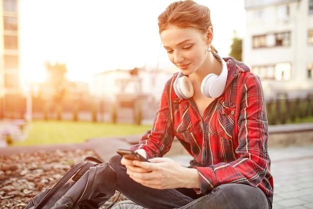ヘッドフォンで音楽を聴く若い赤毛の女子学生の肖像画