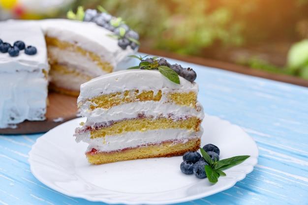 木製の素朴なテーブルの上に食欲をそそるチーズケーキケーキビスケット枕装飾ホワイトクリームブルーベリーとミントスタンド