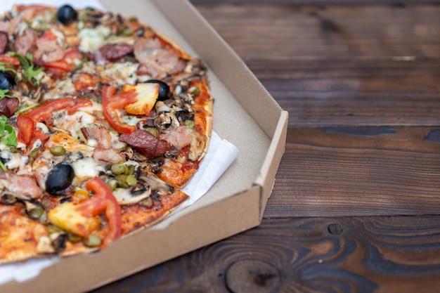 スモークソーセージベーコンミートトマトチーズルッコラ段ボール箱入りの食欲をそそるピザ。コピースペース付き