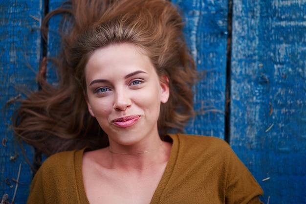 木製の桟橋に横たわっている美しい白人の若い女性