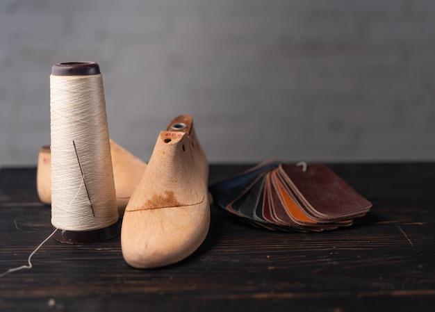 靴とプラスチックの靴の革のサンプルは、暗い木製のテーブルに最後まで