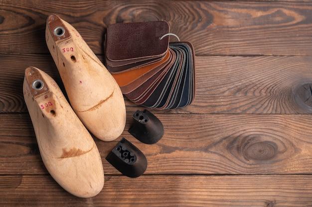 Образцы кожи для обуви и пластиковой обуви последний на темном деревянном столе