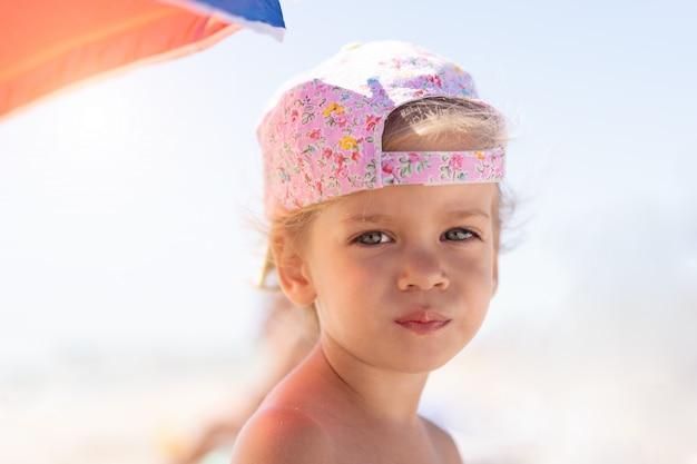 キャップとビーチで小さな白人の女の子
