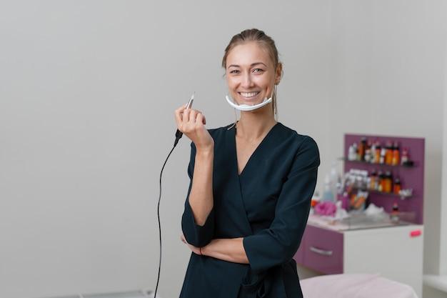 Косметолог стоит в маске и улыбается.