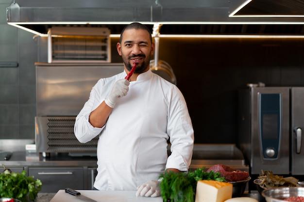 肉の食事を準備するレストランのプロのキッチンに立っている若いアフリカ人シェフ