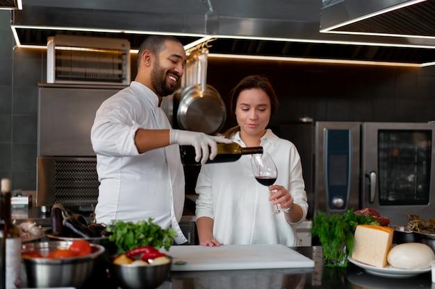Молодой африканский шеф-повар готовит вместе с кавказской девушкой на кухне