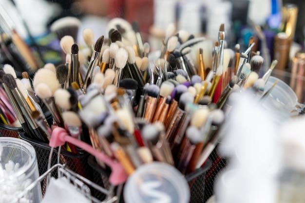 Кисти для макияжа, случайно стоящие в контейнерах на рабочем месте визажиста