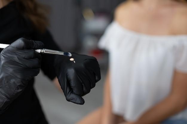 Девушка молодого косметолога кавказская держит модельную коррекцию брови