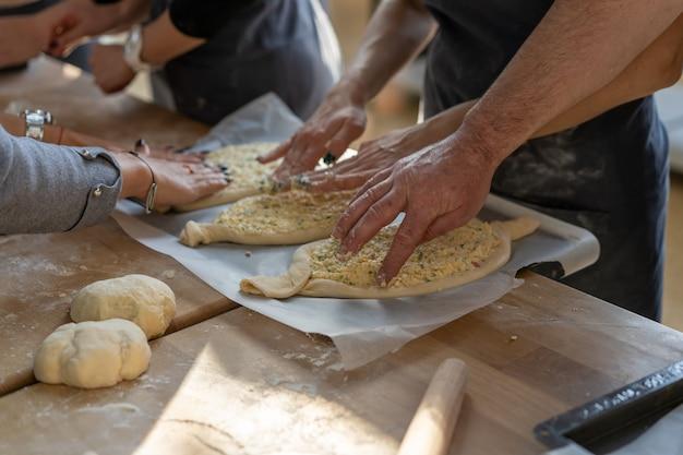 Кулинарный мастер-класс. крупный план рук людей подготавливая хачапури. традиционный грузинский сырный хлеб. грузинская еда