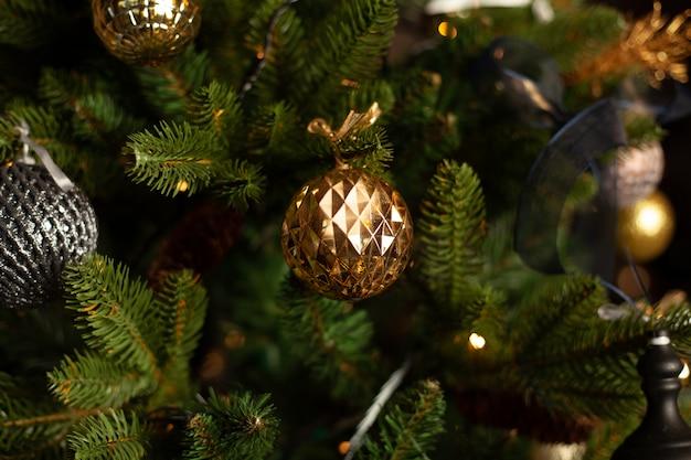 金のボールと青い弓で飾られたクリスマスツリーのクローズアップ。クリスマス休暇の概念