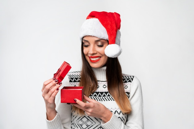 白い壁に赤いサンタ帽子で肖像画美しい白人女性を閉じます。クリスマス正月コンセプトポジティブな感情を笑顔驚いたかわいい女性の歯が小さな赤いギフトボックスを開く