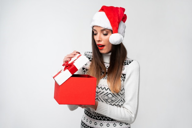 白い壁に赤いサンタ帽子で肖像画美しい白人女性を閉じます。クリスマス正月コンセプトポジティブな感情を笑って驚いたかわいい女性の歯が大きな赤いギフトボックスを開く