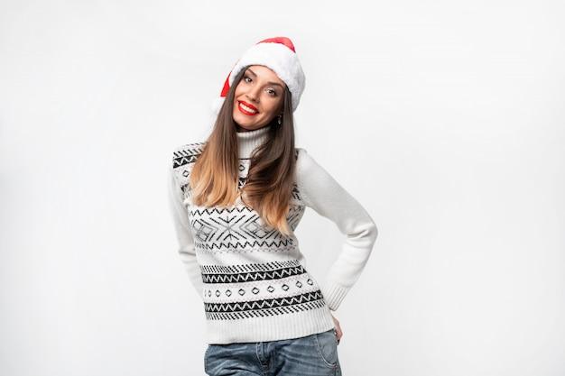 白い壁に赤いサンタ帽子で肖像画美しい白人女性を閉じます。クリスマス新年のコンセプト。無料のコピースペースで肯定的な感情を笑顔かわいい女性の歯