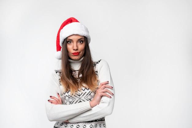 白い壁に赤いサンタ帽子で肖像画美しい白人女性を閉じます。クリスマス新年のコンセプト。