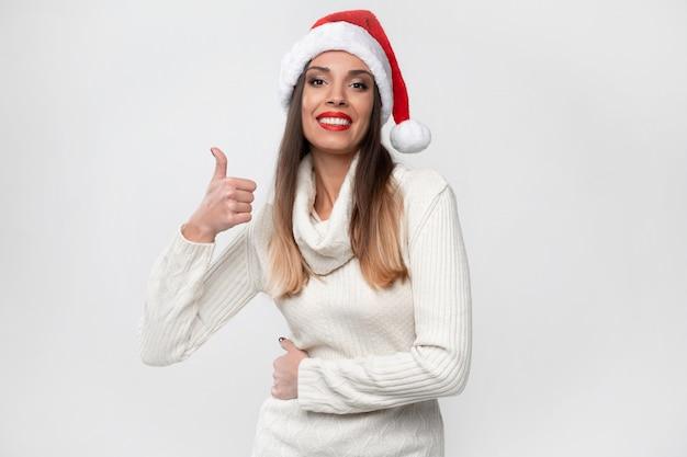 白い壁に赤いサンタ帽子で肖像画美しい白人女性を閉じます。クリスマス新年のコンセプト。肯定的な感情を笑っているかわいい女性の歯親指を表示