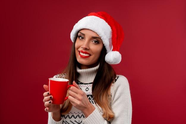 赤い壁に赤いサンタ帽子で肖像画美しい白人女性を閉じます。クリスマス新年のコンセプト。かわいい女性の歯の手でコーヒーの赤カップと肯定的な感情を笑顔