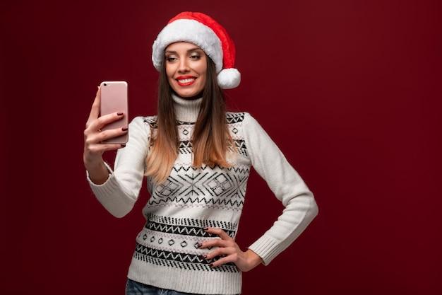 赤い壁に赤いサンタ帽子で肖像画美しい白人女性を閉じます。クリスマス新年のコンセプト。無料のコピースペースで肯定的な感情を笑顔かわいい女性の歯