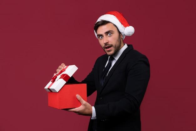 ビジネススーツとプレゼントボックスとサンタ帽子で若いハンサムな男